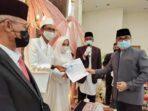 INOVASI: Kepala Disdukcapil Kota Palangka Raya, H. Efendie, menyerahkan dokumen kependudukan kepada warga yang baru saja menikah, belum lama ini.FOTO:HUMAS