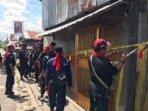 TANDA ADAT: Sejumlah anggota Batamad Kabupaten Kotim melakukan pemasangan tanda adat di Toko Miras Cawang Mas di jalan Tjilik Riwut Sampit, Sabtu (19/6)./BAHRI