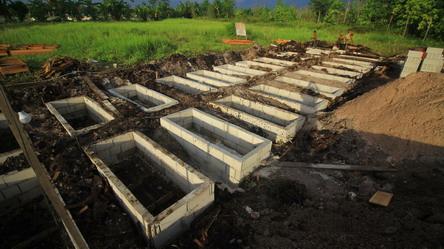 PEMAKAMAN: Pekerja menyiapkan liang kubur untuk memakamkan jenazah pasien Covid-19 di TPU Jalan Tjilik Riwut Km 12, Palangka Raya, Rabu (21/7/2021). FOTO: DENAR