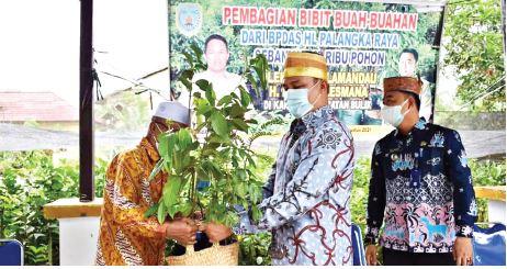 SALURKAN BANTUAN : Bupati Lamandau H Hendra Lesmana (kanan) menyalurkan bantuan bibit buah-buahan kepada perwakilan warga di kawasan Kantor Kecamatan Bulik, Kabupaten Lamandau, belum lama ini