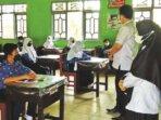 PTM: Kadisdik Kotim, Suparmadi didampingi Kepala Sekolah SMP 3 Sampit, Hj Siti Hadijah melihat proses PTM yang digelar secara ketat, Rabu (1/9).