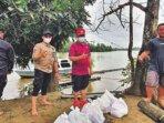 BERI BANTUAN: Bupati Seruyan, Yulhaidir (dua dari kanan) turun ke daerah yang terdampak banjir untuk menyerahkan paket bantuan, baru baru ini.