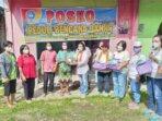 MENYERAHKAN : Anggota Dewan Perwakilan Rakyat Daerah (DPRD) Kabupaten Gunung Mas Rayaniatie Djangkan (baju putih pakai syal), saat memberikan bantuan kepada masyarakat terdampak banjir, belum lama ini.