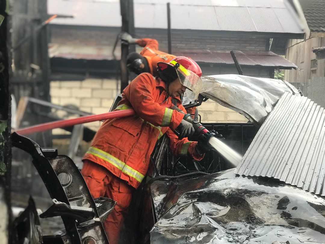 DIPADAMKAN: Petugas Damkar berusaha memadamkan api yang membakar bengkel di Jalan Kawitan, Rabu (6/10).