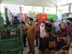 CEK SARPRAS: Bupati Sukamara H Windu Subagio mengecek mesin pencacah sampah milik TPS 3R Bukit Patung Jaya saat meresmikan TPS 3R di Desa Bangun Jaya, belum lama tadi.
