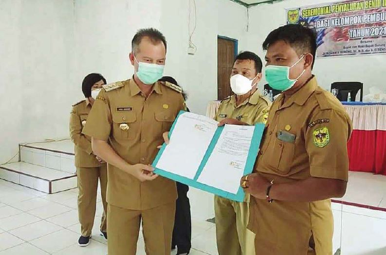 SERAHKAN BANTUAN : Bupati Gunung Mas Jaya Samaya Monong (kiri) menyerahkan bantuan bibit ikan dan bantuan sosial bagi korban banjir di Desa Hurung Bunut, belum lama ini.